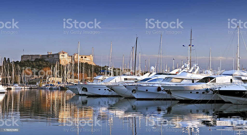Yachts in Antibes harbor with fortress on hillside stock photo