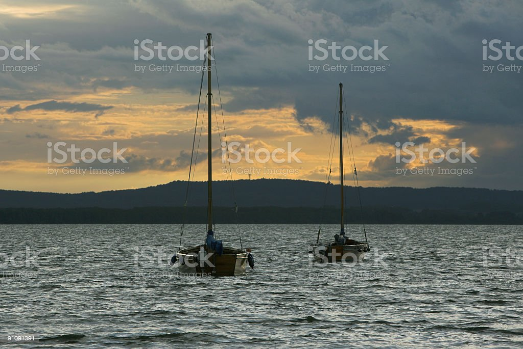 Yachts on lake and majestic cloudscape at sunset royalty-free stock photo
