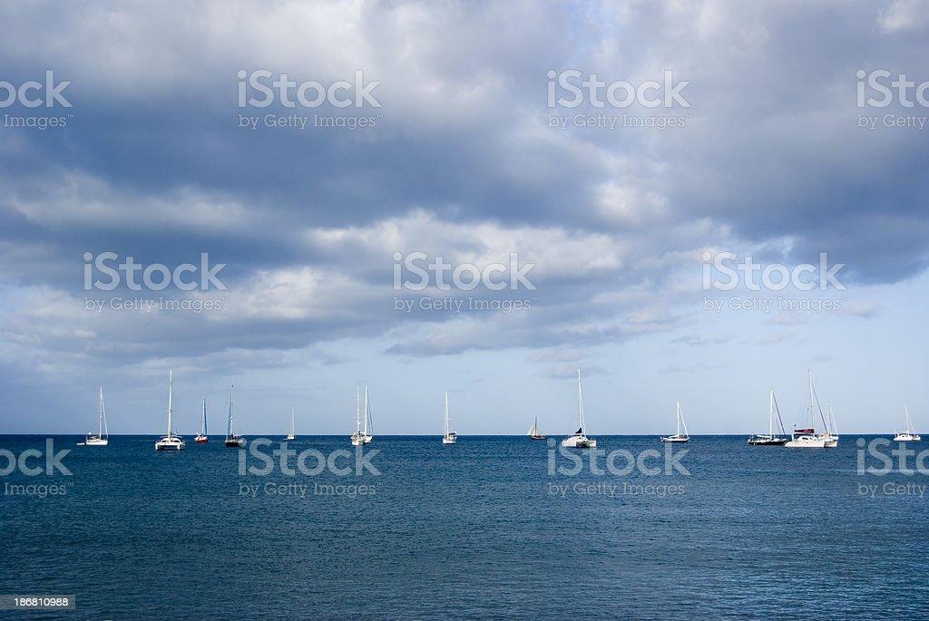 yachts sailing under cloudy skies against horizon royalty-free stock photo