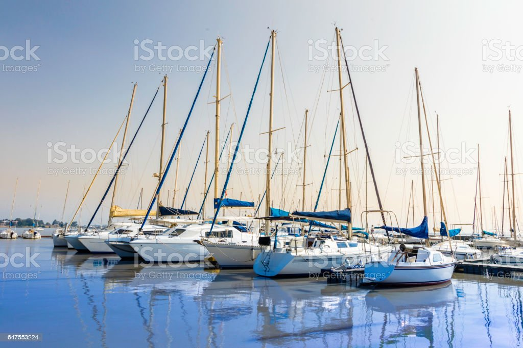 Yachts seen anchored at a jetty in a lake stock photo
