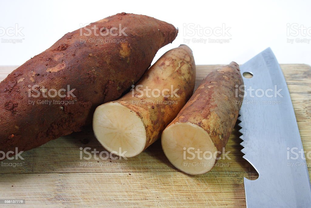 Yacon roots and chef knife on wooden board stock photo