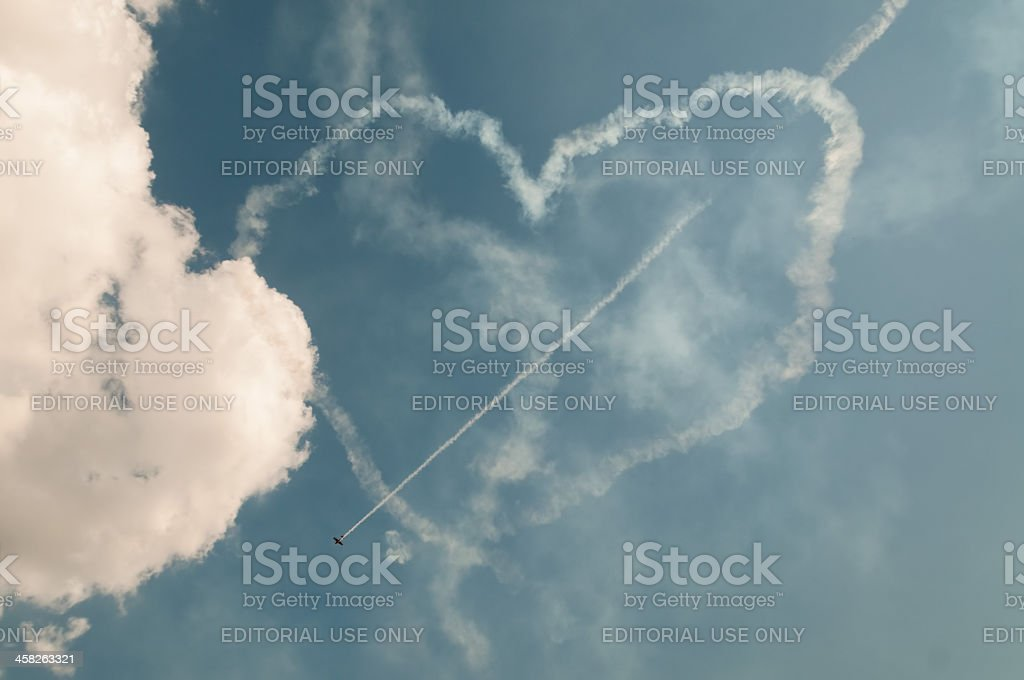 Yak-52 aircraft draws arrow in heart formed by white smokes royalty-free stock photo