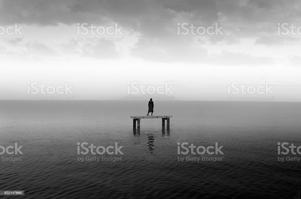 yang girl stand along at sea on cement plate stock photo