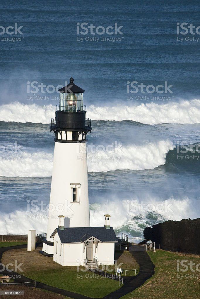 Yaquina Head Lighthouse sits before crashing surf on Oregon Coast stock photo