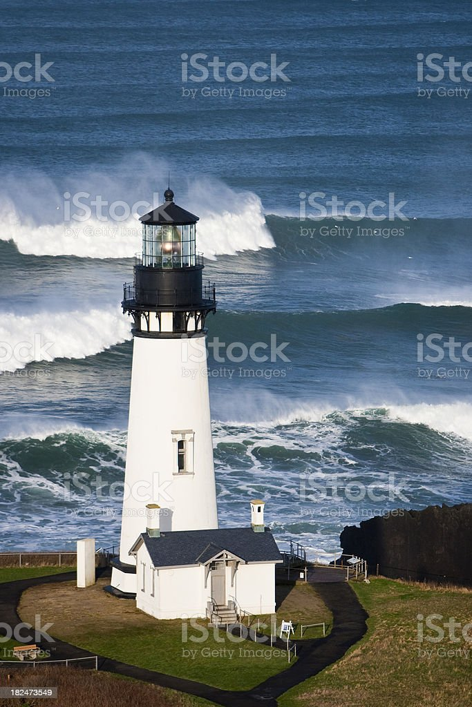 Yaquina Head Lighthouse vertical closeup as surf crashes behind beacon stock photo