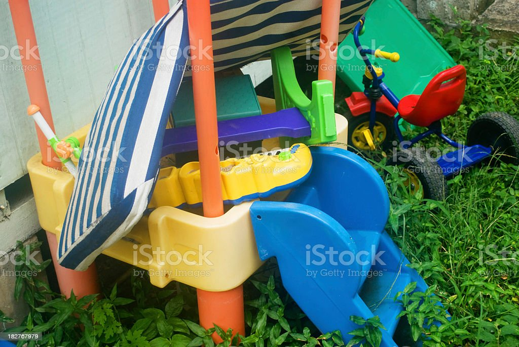 yard sale - abandoned group of childrens toys on grass royalty-free stock photo