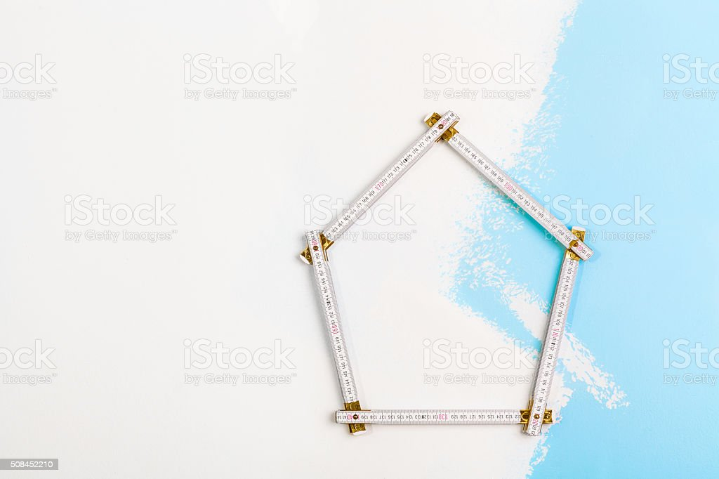 yardstick shaped as a house on wall stock photo