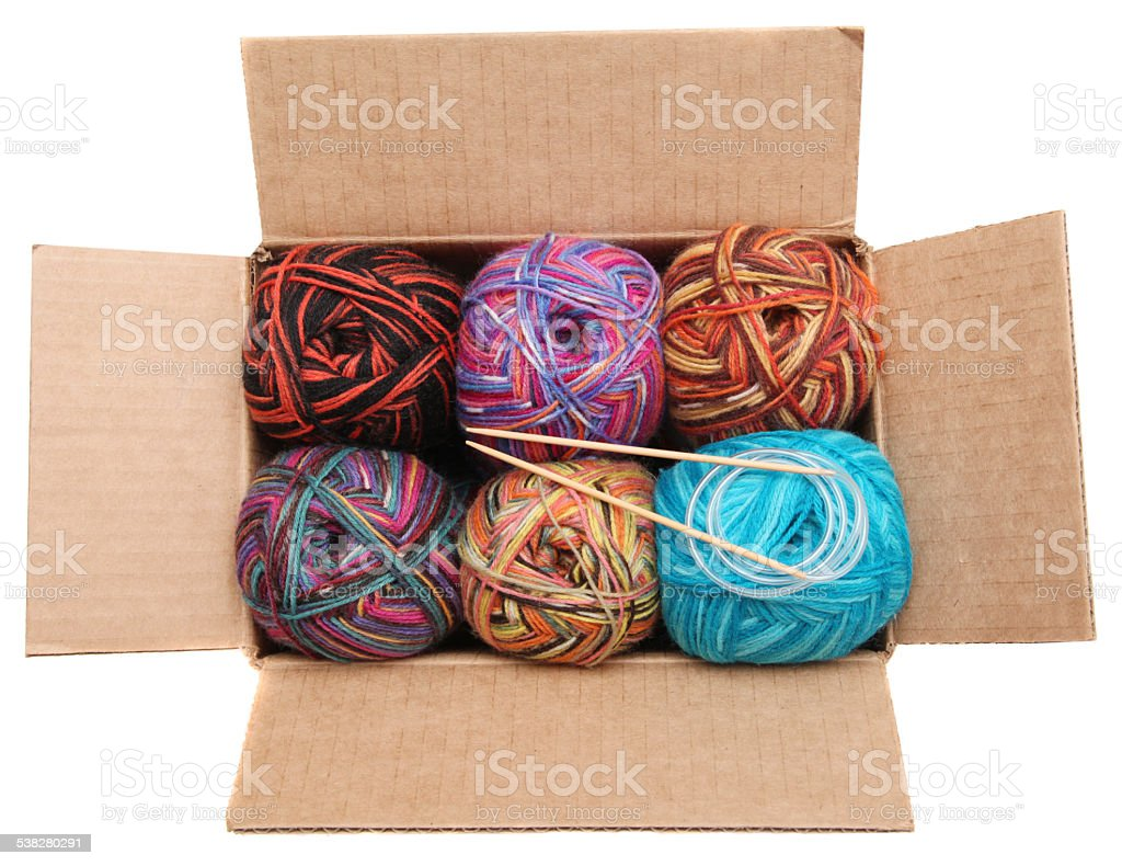Yarn and knitting needles in an opened box stock photo