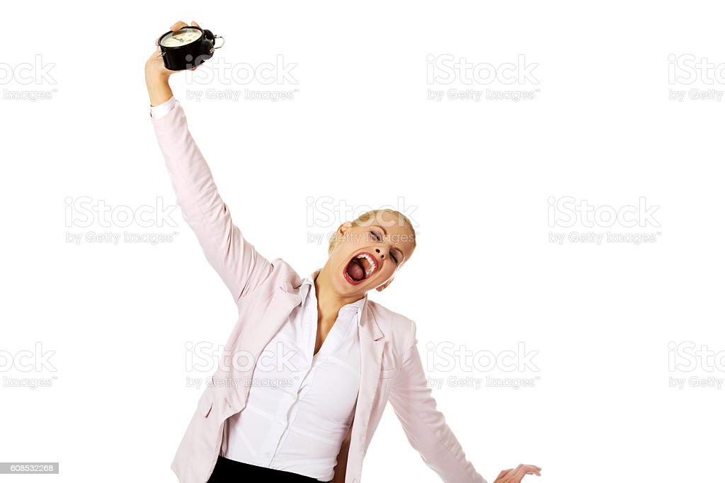 Yawning business woman holding alarm clock stock photo