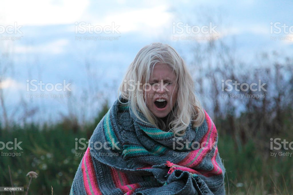 yawning girl in poncho stock photo