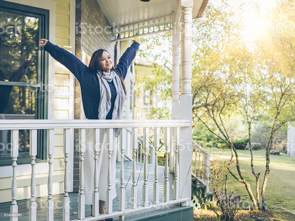 yawning woman standing at porch stock photo