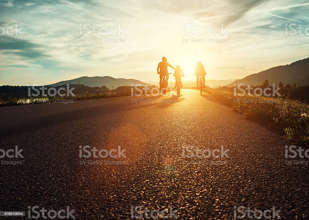 Сyclists family traveling on the road at sunset stock photo