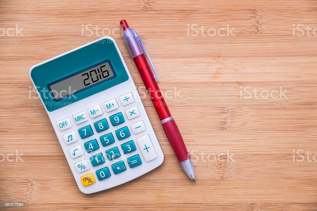 Year 2016 written on a calculator and a pen on wood stock photo