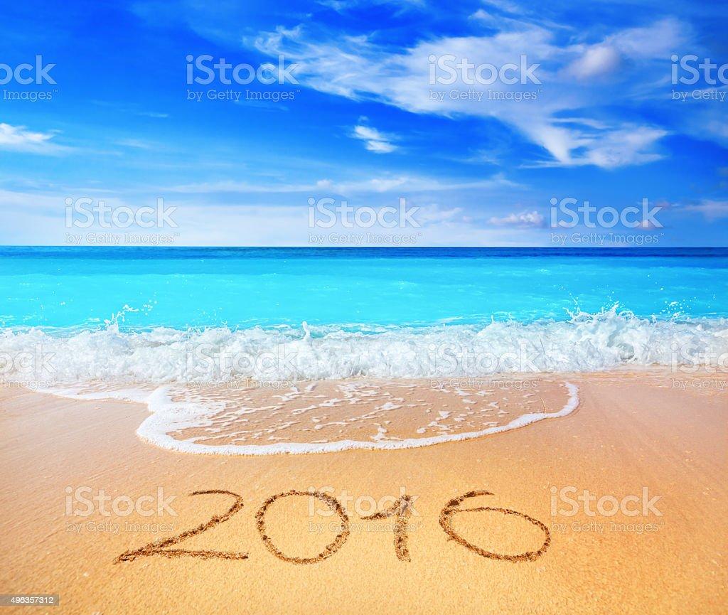Year 2016 written on sandy beach stock photo