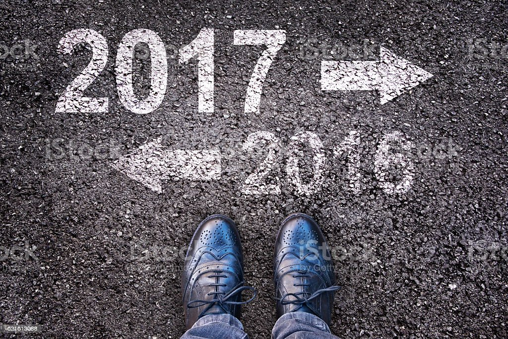 Year 2017 and 2016 written on an asphalt road stock photo
