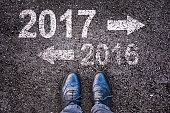 Year 2017 and 2016 written on an asphalt road