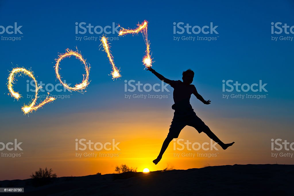 year 2017 written with sparkles, silhouette of a boy jumping stock photo