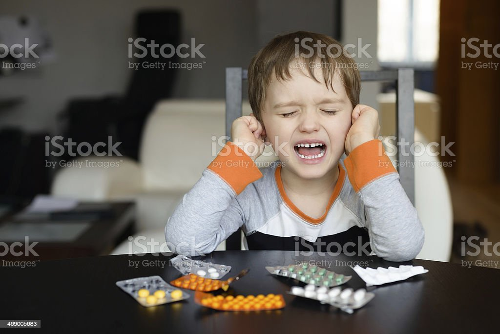 4 year old boy crying before swallowing medication stock photo