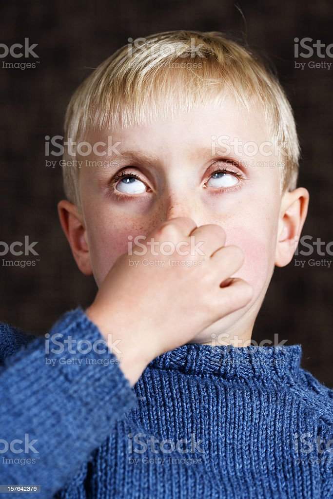 7 year old boy holds nose and rolls eyes, phew! royalty-free stock photo