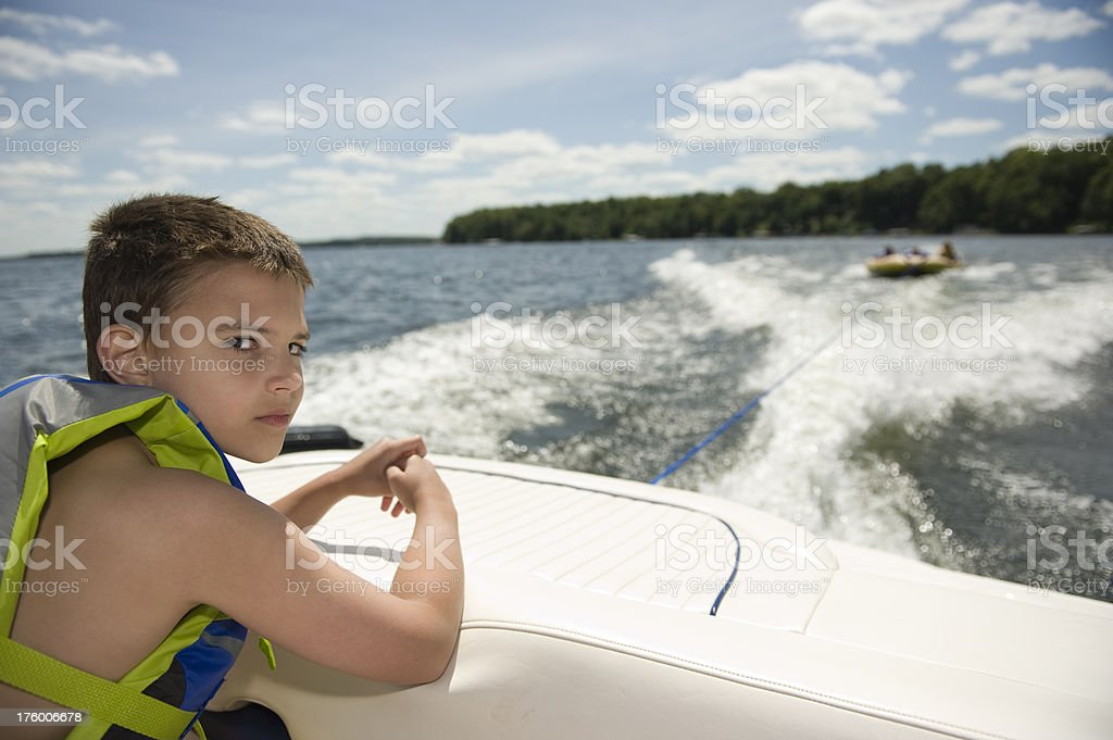 8 Year old boy riding on a boat royalty-free stock photo