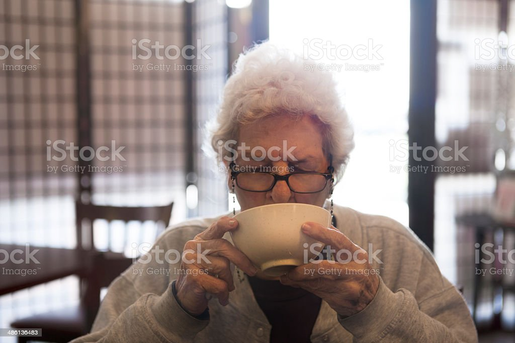 91 Year Old Woman Drinking Soup from Bowl stock photo