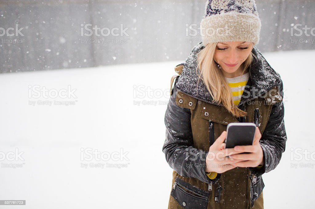 20-30 year old woman texting in the snow stock photo