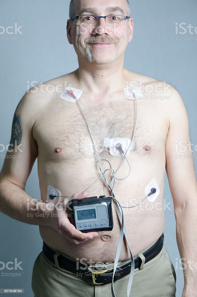50 year-old man with 5 sensors with holter monitor stock photo
