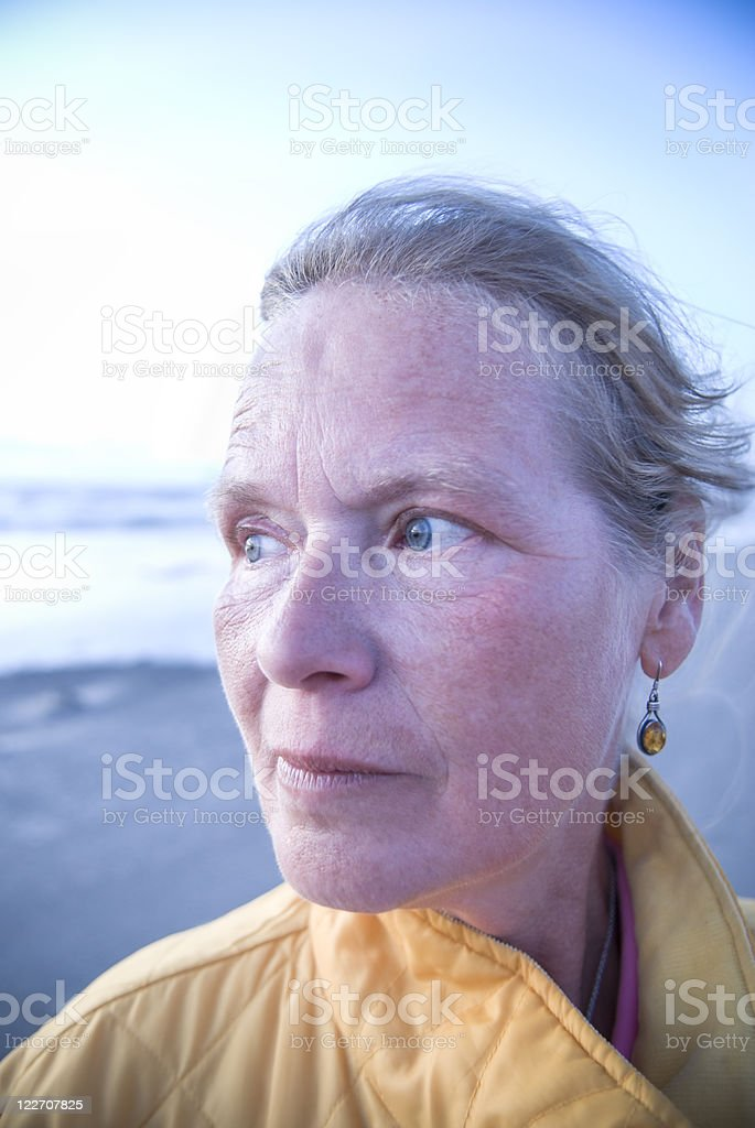 50 year-old woman looking at sunset over ocean, emotional royalty-free stock photo