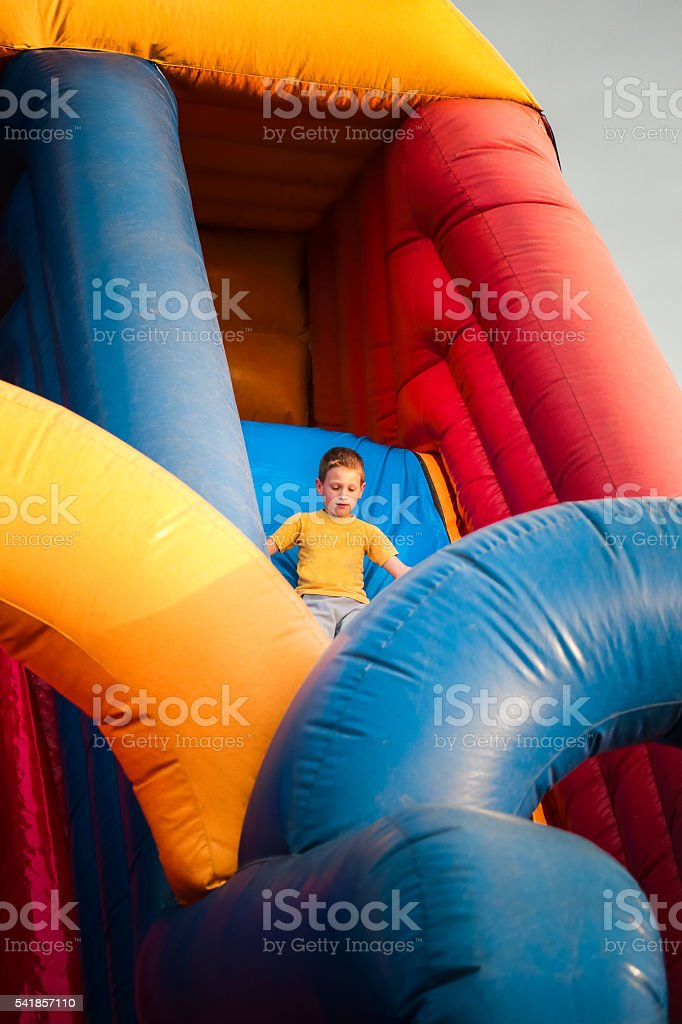 7 years boy play on inflatable bouncy castle slide stock photo