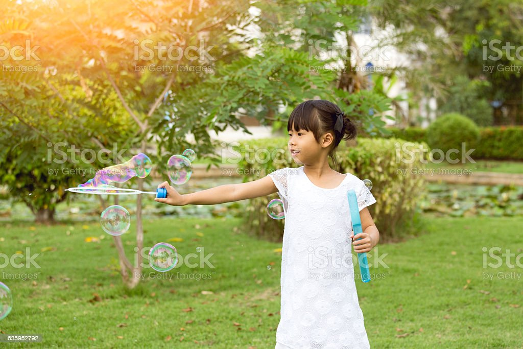 7 years old Asian girl play soap bubble in park stock photo