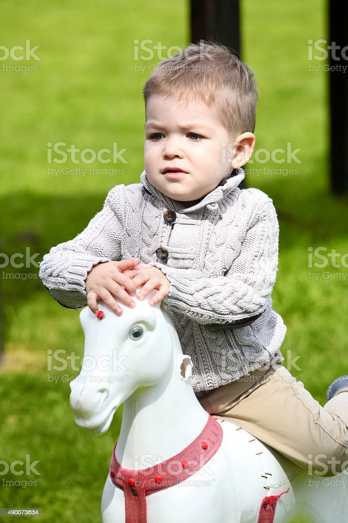 2 years old Baby boy playing with horse stock photo