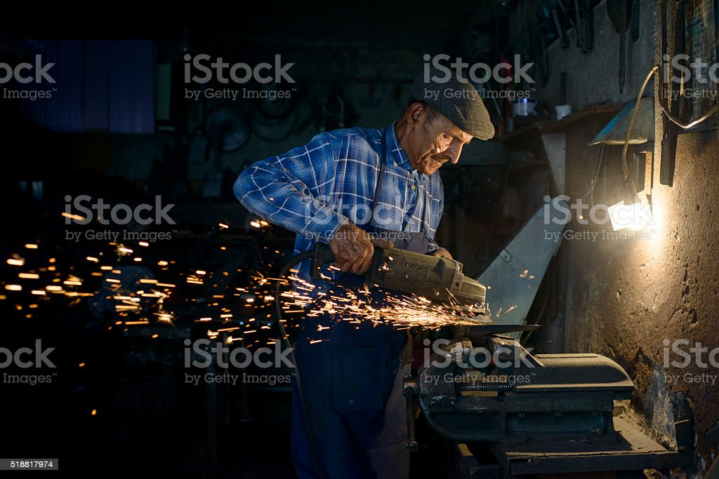 90 years old  blacksmith grinding axe in his workshop stock photo