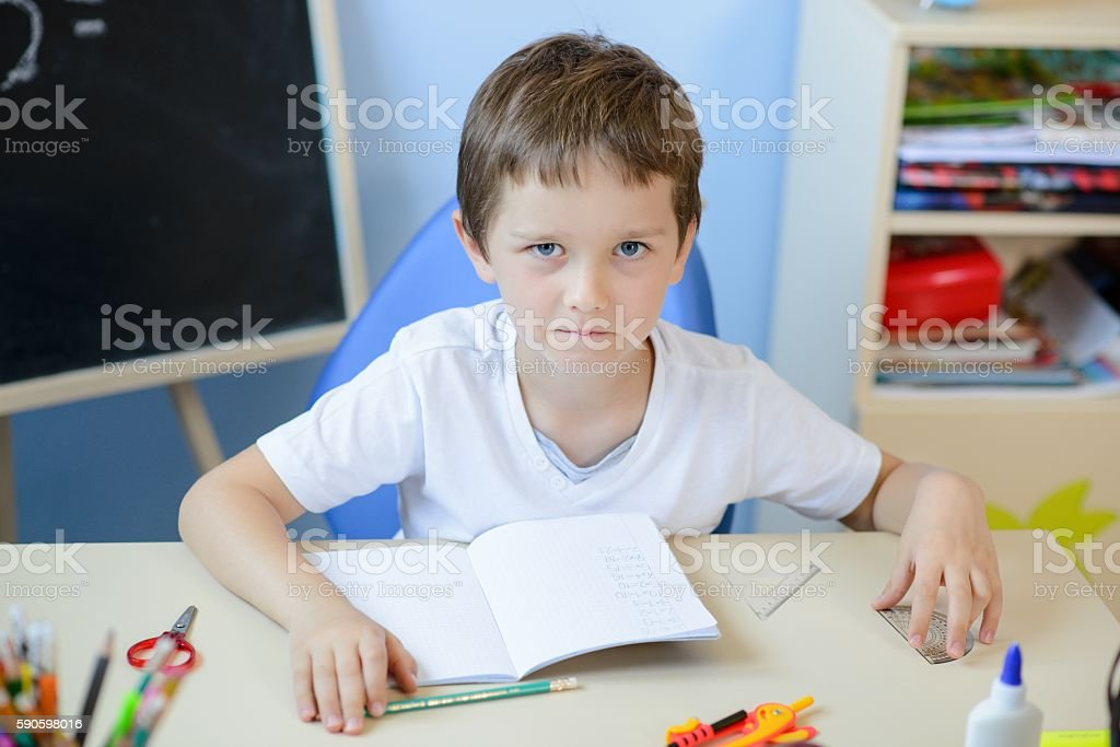 7 years old boy doing his homework stock photo