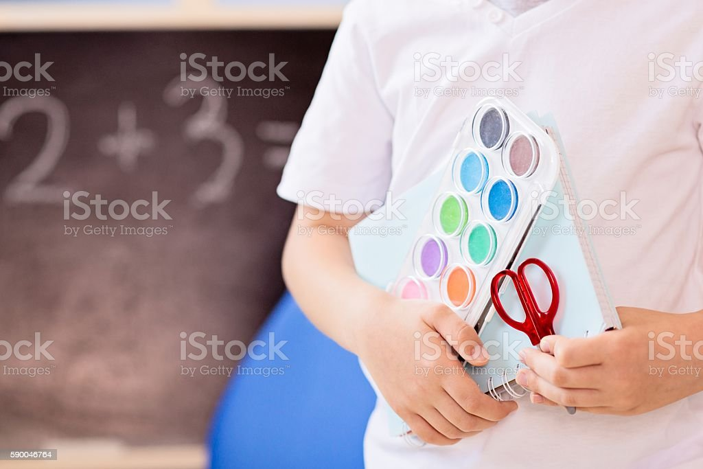 7 years old boy holding school accesories in his hand stock photo