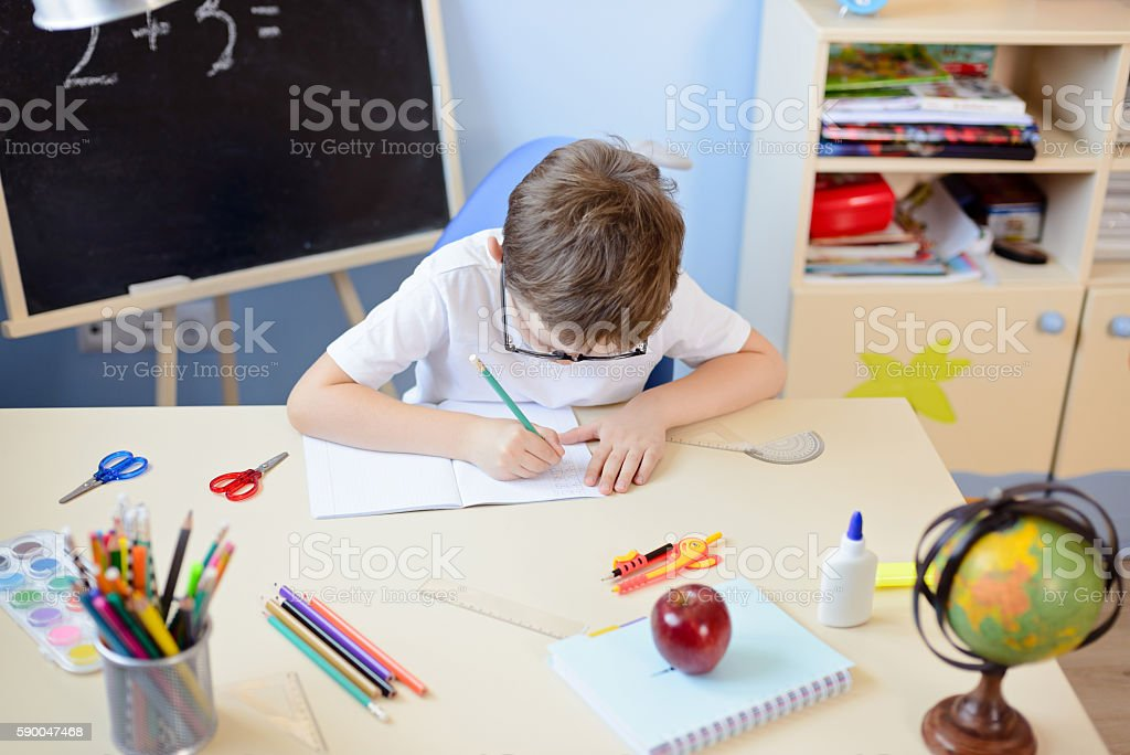 7 years old boy solves multiplication table in his copybook. stock photo