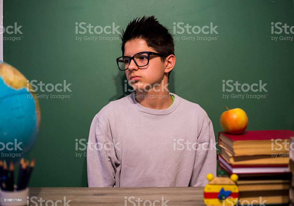 15 years old children boy sitting at the wooden desk. stock photo