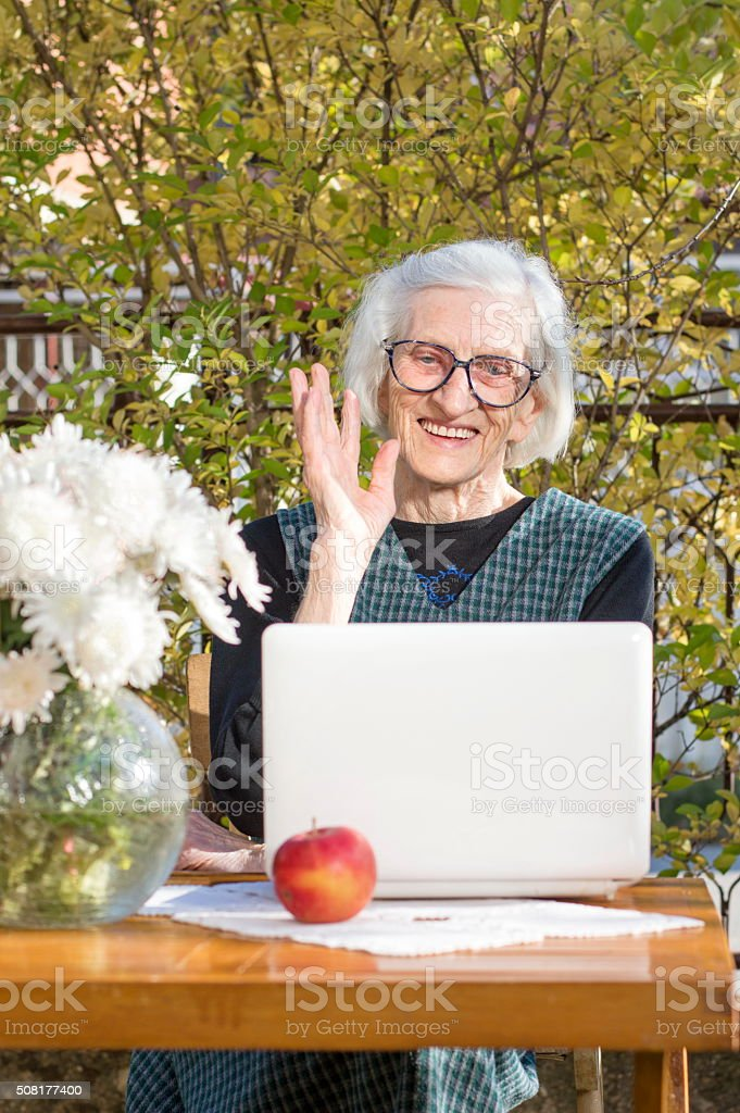 90 years old woman waving while having a video call stock photo