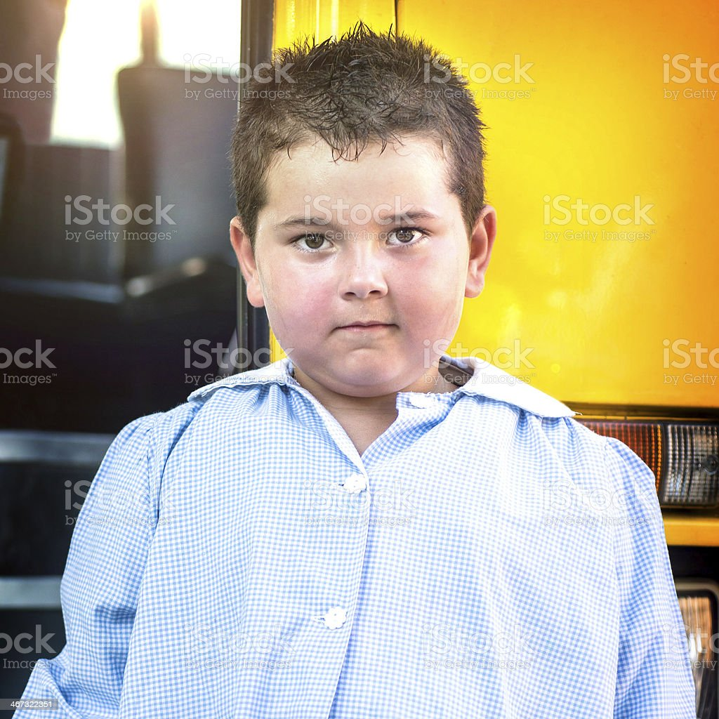 5 years-old Child in front a School Bus with Apron royalty-free stock photo
