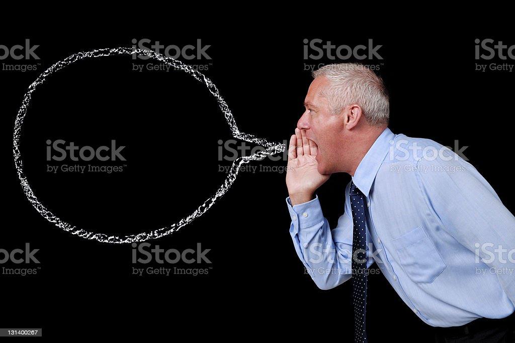 Yelling businessman against blackboard with speech bubble stock photo