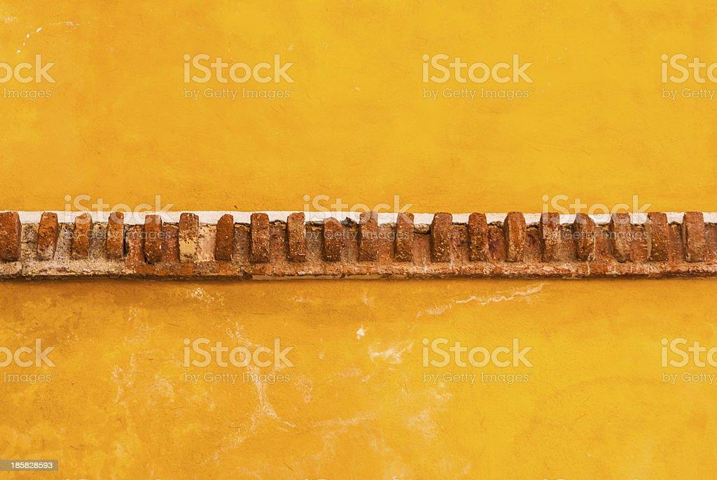 Yellow adobe wall with brick trim royalty-free stock photo
