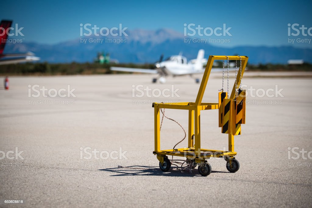 A yellow aircraft chocks and fire extinguisher carrier on a small airport. Aircraft chocks are hanging on the carriers handle. Small aircraft and scenic view on the background. stock photo