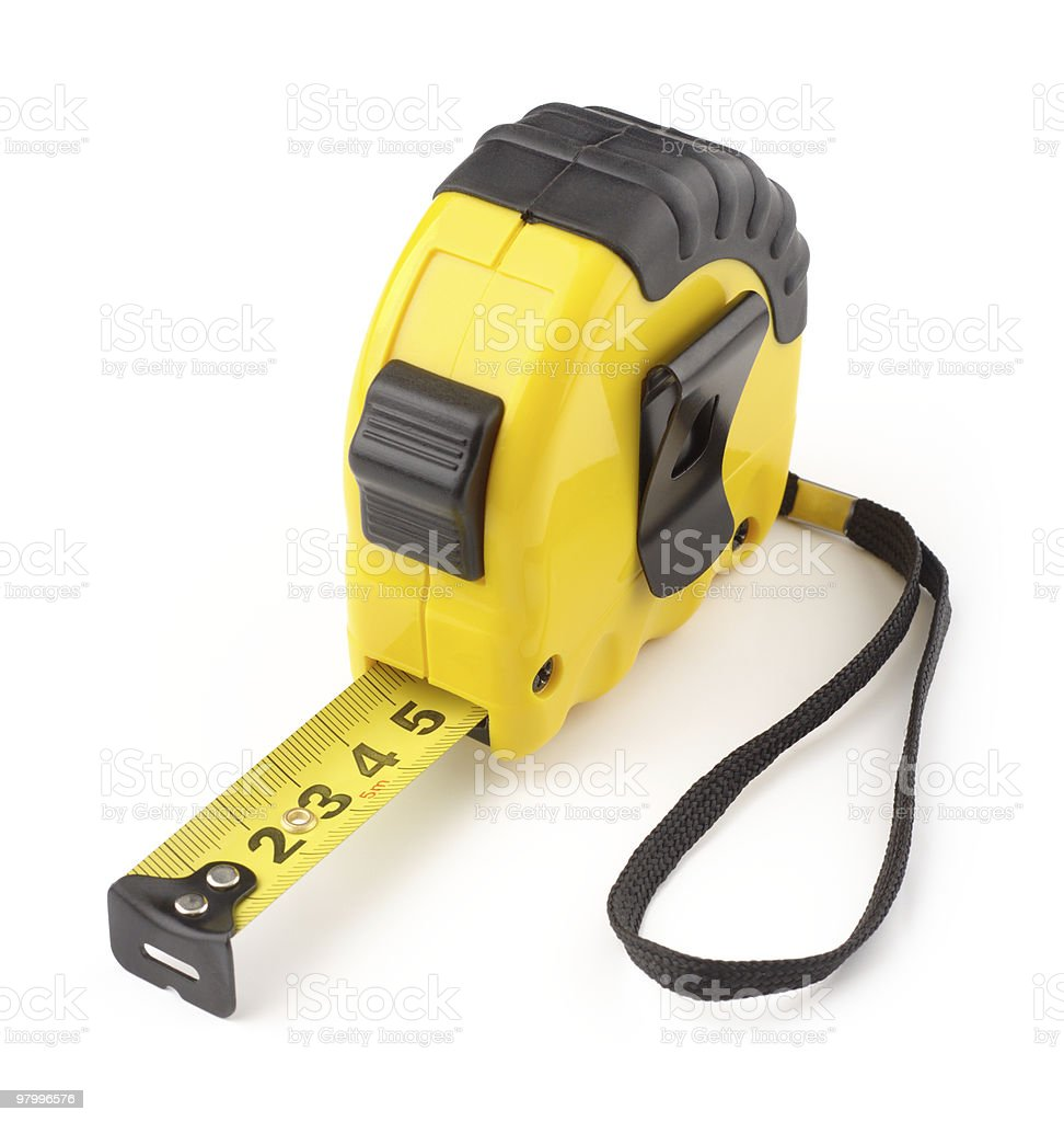 A yellow and black tape measure opened to five inches stock photo