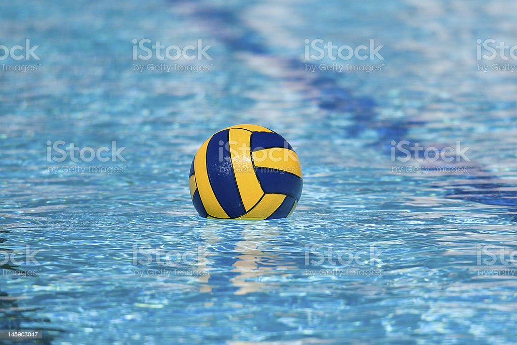 A yellow and blue ball floating in a pool stock photo