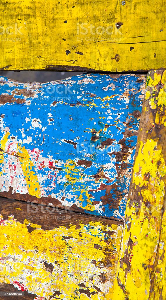 yellow and blue chipped paint on old wooden cart stock photo