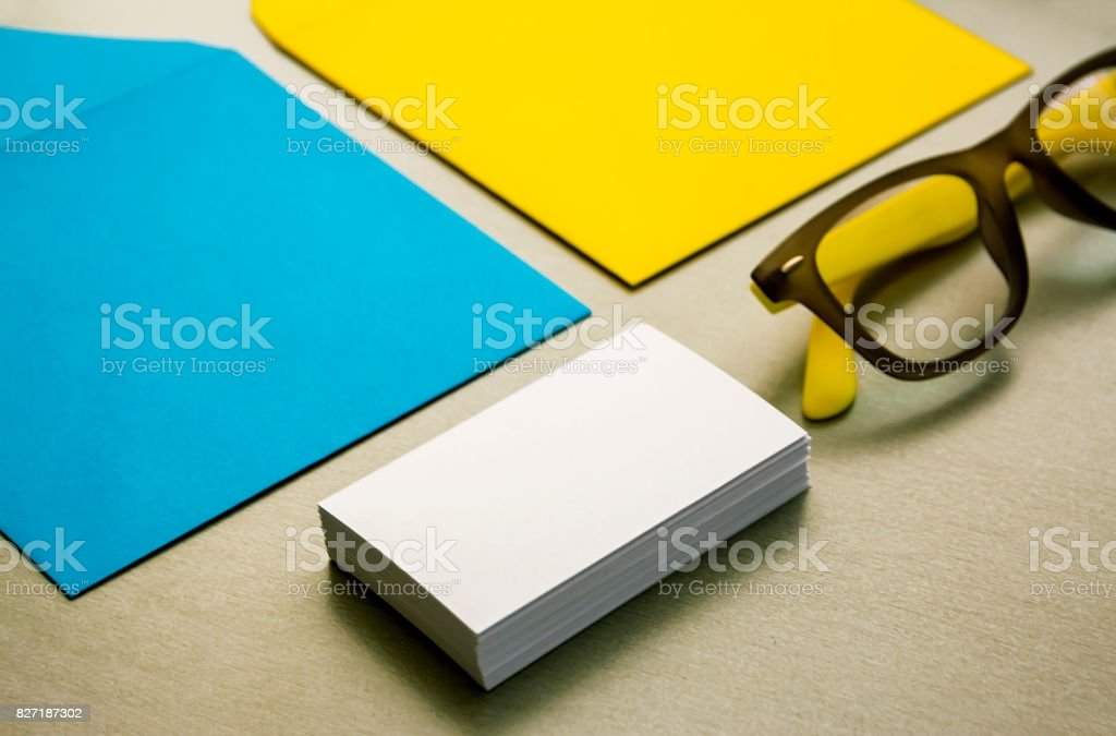 Yellow and blue envelope, business cards and glasses stock photo