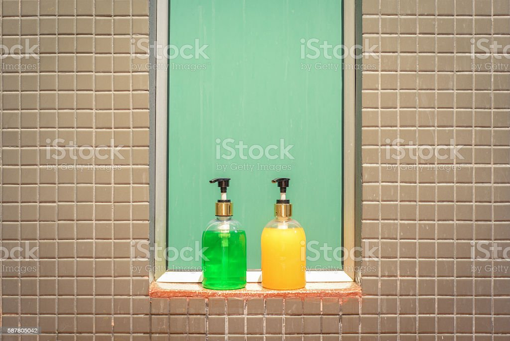 Yellow and green bottles of liquid soap and shampoo stock photo