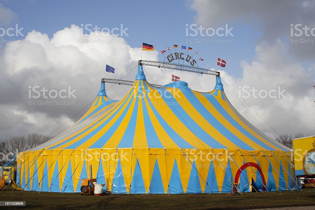 Yellow and light blue circus tent over a cloudy sky stock photo
