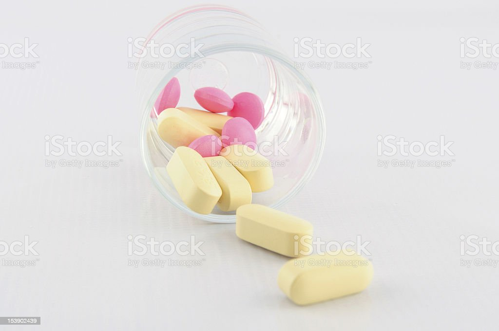 Yellow and pink tablet in dosage glass royalty-free stock photo