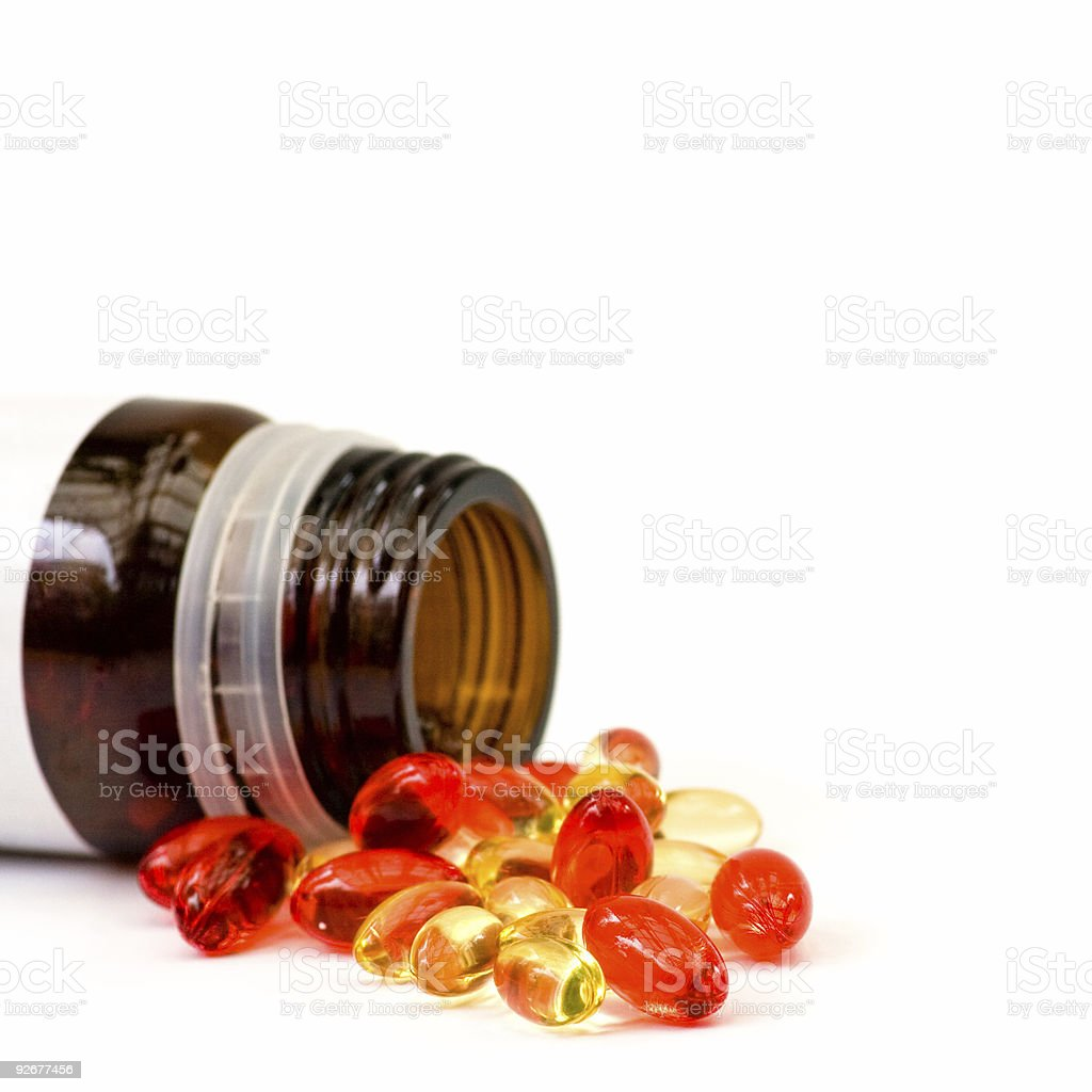 Yellow and red pills on a white background stock photo