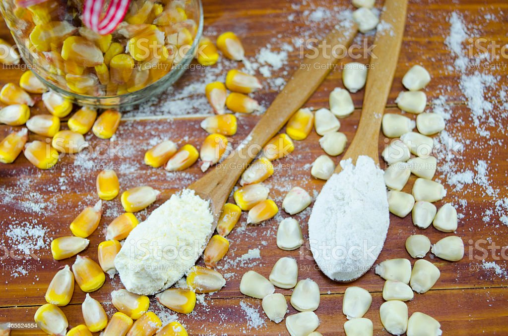 Yellow and white corn and flour in spoons royalty-free stock photo